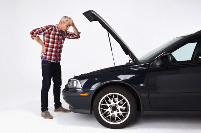 Homme désamparé qui regarde sous le capot d'une voiture en panne